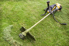 Petrol trimmer is on the sloped lawn. In the garden Stock Image