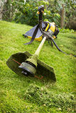 Petrol trimmer on the sloped lawn. In the garden Stock Images
