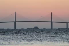 Petroleiro sob a ponte de Skyway da luz do sol Foto de Stock Royalty Free