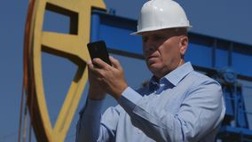 Petroleum Engineer Working in Extracting Oil Industry Using Mobile Phone Communi stock photography