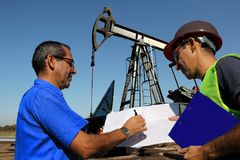 Petroleum Engineers Discussing Issues at Work. Petroleum engineers with laptop and blueprint in an oilfield manage the technical aspects related to exploration stock photography