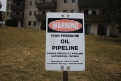 Petroleum pipeline warning sign in green grassy meadow. stock photos