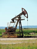 Petroleum pump, Lithuania. A small old rusty petroleum pump equipment standing in a field stock images
