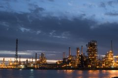 Petroleum refinery factory on water coast at dusk Royalty Free Stock Image