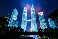 Petronas eleva-se fundo atrás da ponte da silhueta Fotos de Stock