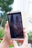 Petronas Towers. KUALA LUMPUR, MALAYSIA - AUGUST 18,2016: Tourist makes photo of Petronas Towers on HTC smart phone Stock Image