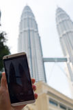 Petronas Towers. KUALA LUMPUR, MALAYSIA - AUGUST 18,2016: Tourist makes photo of Petronas Towers on HTC smart phone Royalty Free Stock Images