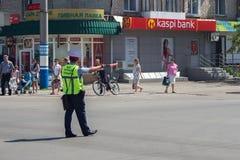 PETROPAVL, KAZACHSTAN - JULI 24, 2015: De wegpolitieman van Kazachstan in eenvormig regelend verkeer in de stad royalty-vrije stock fotografie