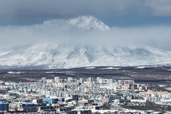 Petropavlovsk-Kamchatsky City and active Koryak Volcano. Winter cityscape: top view of City Petropavlovsk-Kamchatsky and active Koryaksky Volcano on a cloudy day Royalty Free Stock Photography