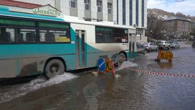 Autobus driving on road over deep puddle and splashing water from wheels. PETROPAVLOVSK KAMCHATSKY CITY, KAMCHATKA PENINSULA, RUSSIA - 12 MAY, 2018: City autobus stock video footage