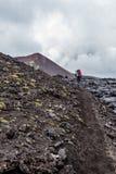 Petropavlovsk-Kamchatsky region, Russia - August 11, 2013: Tourist going up on a lava field near Tolbachik Volcano stock photography
