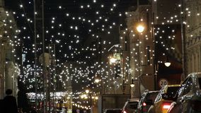 Petrovka street in Moscow city center decorated with garlands tiny lights for Christmas holidays. Traffic jam, taxi cars.  stock video