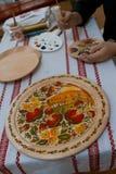 Petrykivka painting style wooden plate, Ukrainian folk art, man`s hands handpainting on a plate, ethnographic master class. Vinnytsia, Ukraine - 19.03.2018 stock photo