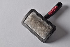 Pets brush. Close up of an used hairbrush to brush pets,  on gray background Royalty Free Stock Image
