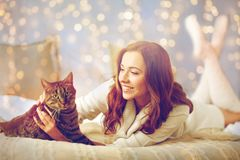 Happy young woman with cat lying in bed at home Stock Photo