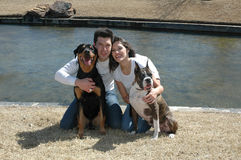 Pets are Family. Happy married couple taking pictures with their dogs in the park Royalty Free Stock Images