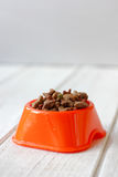 Pets food on cat bowl. Dry feed on orange bowl. Stock Images