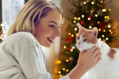 Happy young woman with cat at home on christmas royalty free stock photo