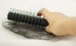 Pettine dei capelli di perdita della tenuta della mano delle donne fotografia stock
