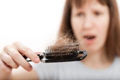 Pettine dei capelli di perdita in mano delle donne fotografie stock libere da diritti