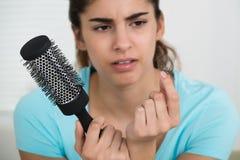 Pettine della tenuta della donna mentre esaminando perdita di capelli Immagine Stock