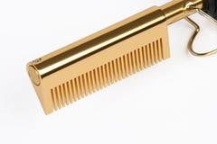 Pettine di raddrizzamento dorato Immagini Stock