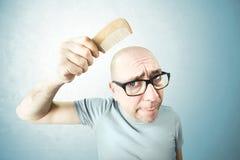 Pettine nostalgico dell'uomo la sua testa calva Fotografia Stock