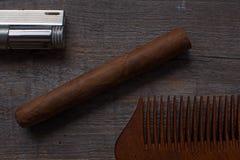 Pettine per le bugie sigar e e dell'accendino di una barba, su un fondo di legno immagini stock libere da diritti