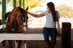 Petting my horse at a ranch. Pretty Hispanic young woman petting and having fun with a horse in a ranch Royalty Free Stock Photos