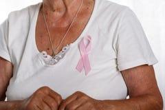 Petto della donna più anziana con il ri rosa appuntato di consapevolezza del cancro al seno fotografia stock libera da diritti