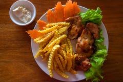 Petto di pollo con le patate fritte e l'insalata sul piatto bianco Foto di vista superiore del pollo fritto sulla tavola di legno fotografia stock libera da diritti