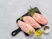 Petto di pollo crudo con basilico fresco e timo sul cuttingboard nero, copyspace Immagine Stock Libera da Diritti