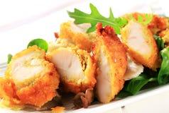 Petto di pollo impanato con i verdi dell'insalata immagine stock