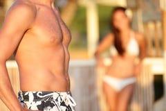 Petto maschio - donna che esamina il torso dell'uomo sulla spiaggia Immagine Stock Libera da Diritti