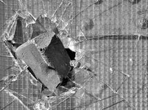 Vandalism. Brick got stuck in a window with reinforced glass in black and white royalty free stock photo
