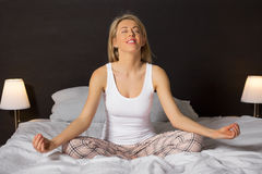 Petty woman sitting in bed and meditating. Petty woman sitting and meditating in her bedroom Royalty Free Stock Photography