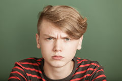 Petulant young teenage boy with a fierce scowl. Glaring at the camera with an intense stare Stock Image