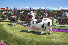 Petunias and sculpture of cow in the Miracle Garden Stock Photography