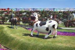 Petunien und Skulptur der Kuh im Wunder arbeiten im Garten Stockfotografie
