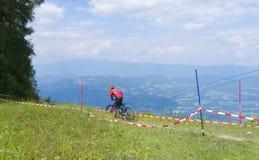 Petzen, Austria - 30 giugno - corridore non identificato del mountainbike di enduro va giù su una fase 3 del campionato di baseba fotografia stock