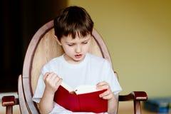 Peu 7 années de garçon lisant un livre Photos libres de droits