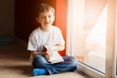 Peu 7 années de garçon lisant un livre Image stock