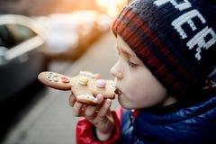 Peu 7 années de garçon mangeant le bonhomme en pain d'épice Photos stock
