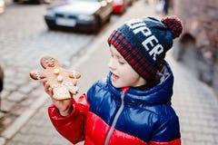 Peu 7 années de garçon mangeant le bonhomme en pain d'épice Images libres de droits
