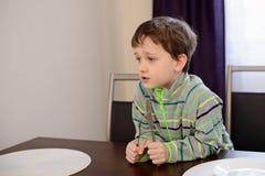 Peu 7 années de garçon tenant la fourchette et le couteau Images libres de droits
