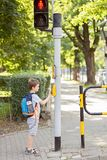 Peu 7 ans d'écolier appuyant sur un bouton sur des feux de signalisation Photo stock