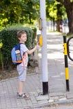 Peu 7 ans d'écolier appuyant sur un bouton sur des feux de signalisation Images libres de droits