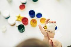 Peu 6 ans de fille avec le jouet de peinture Images stock