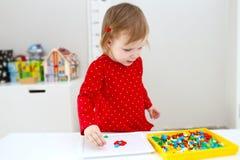 Peu 2 ans de fille joue avec la mosaïque à la maison Photos libres de droits