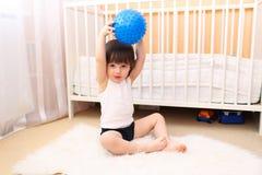 Peu 2 ans de garçon avec la boule de forme physique à la maison Photo stock